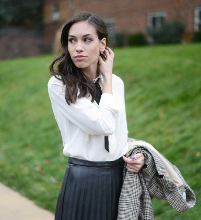 Wellesley & King - a style blog | A classic outfit for work or weekend, a pleated leather skirt and bow tie blouse with a classic plaid overcoat. Click for more style every day style inspiration that YOU can wear! | Bow tie blouse styled by top US fashion blog, Wellesley & King: image of a woman wearing a Banana Republic bow tie blouse, J Crew pleated mini skirt, Banana Republic Factory jacket, J Crew tights, Kate Spade pumps, Nadri earrings, Stella & Dot bracelet and a FOSSIL watch
