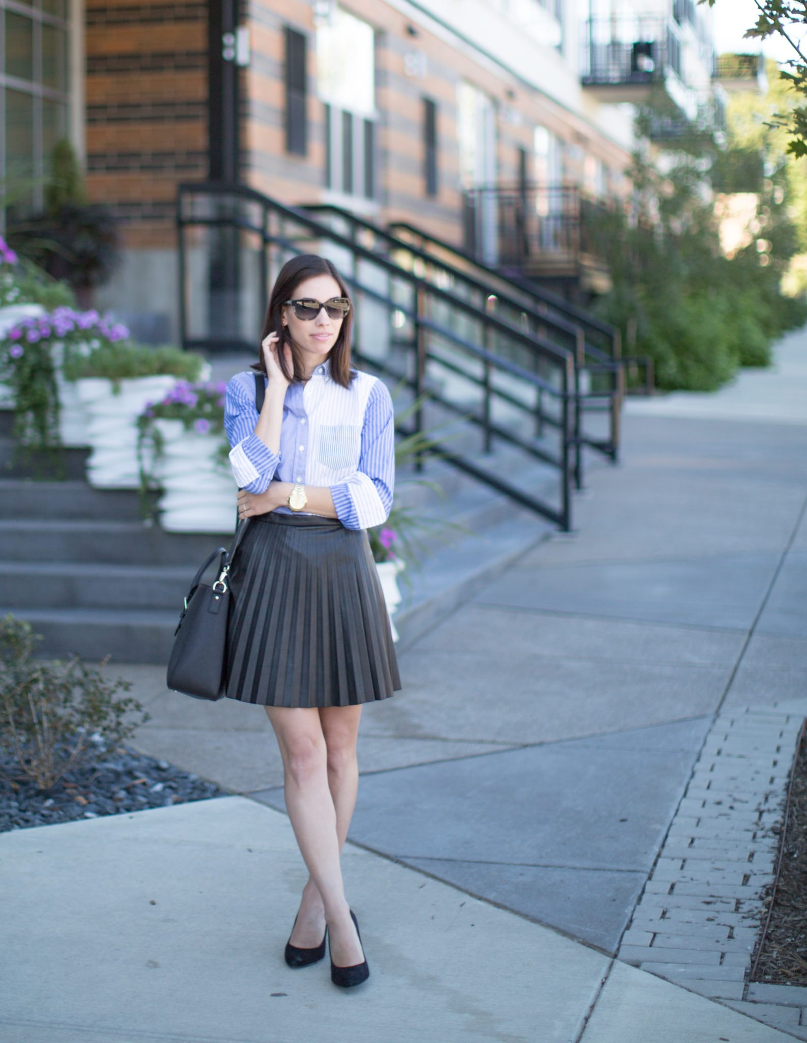 jcrew tuxedo button up blouse pleated leather skirt | J Crew tuxedo shirt styled by top US fashion blog, Wellesley. King: image of a woman wearing a J Crew tuxedo shirt, J Crew pleated mini skirt, Kate Spade cat eye sunglasses and Kate Spade leather satchel