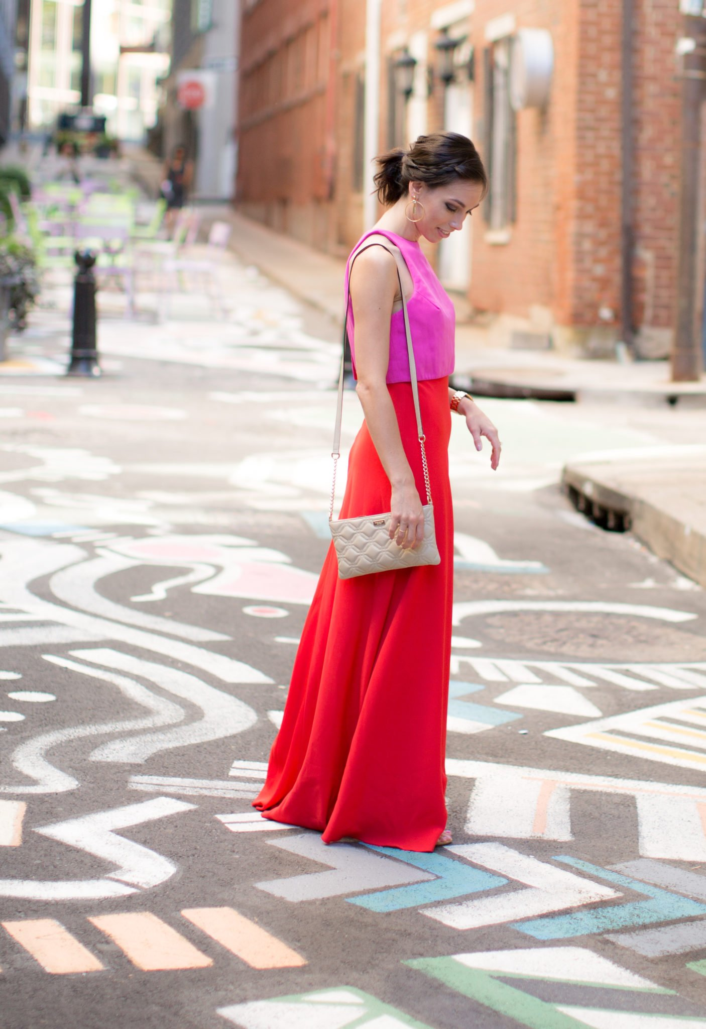 Rent the Runway Jill Stuart red and pink dress | Rent the Runway Wedding Guest Attire featured by top US fashion blog, Wellesley & King: image of a woman wearing a Jill Stuart dress available at Rent the Runway, J Crew hoop earrings, Steve Madden shoes, Marciano bag and Michael Kors watch